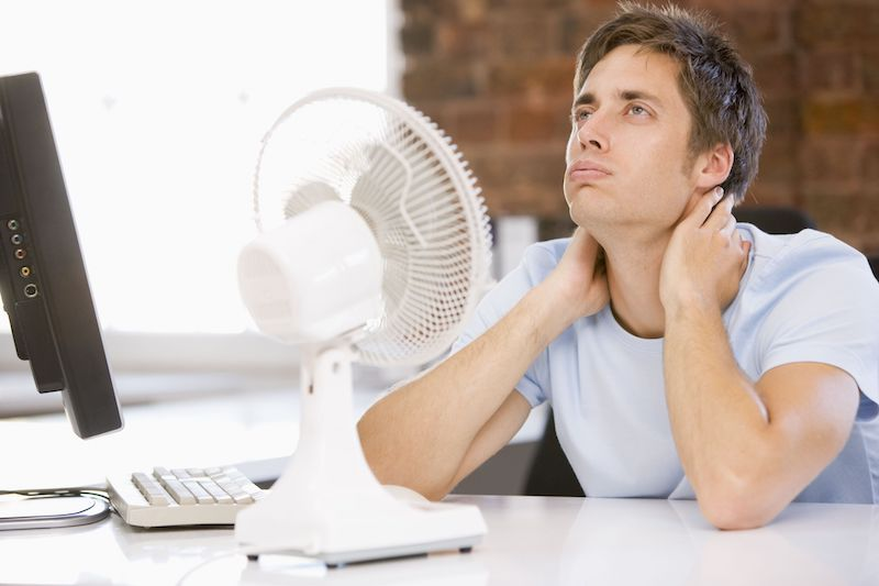 man cooling off with a fan